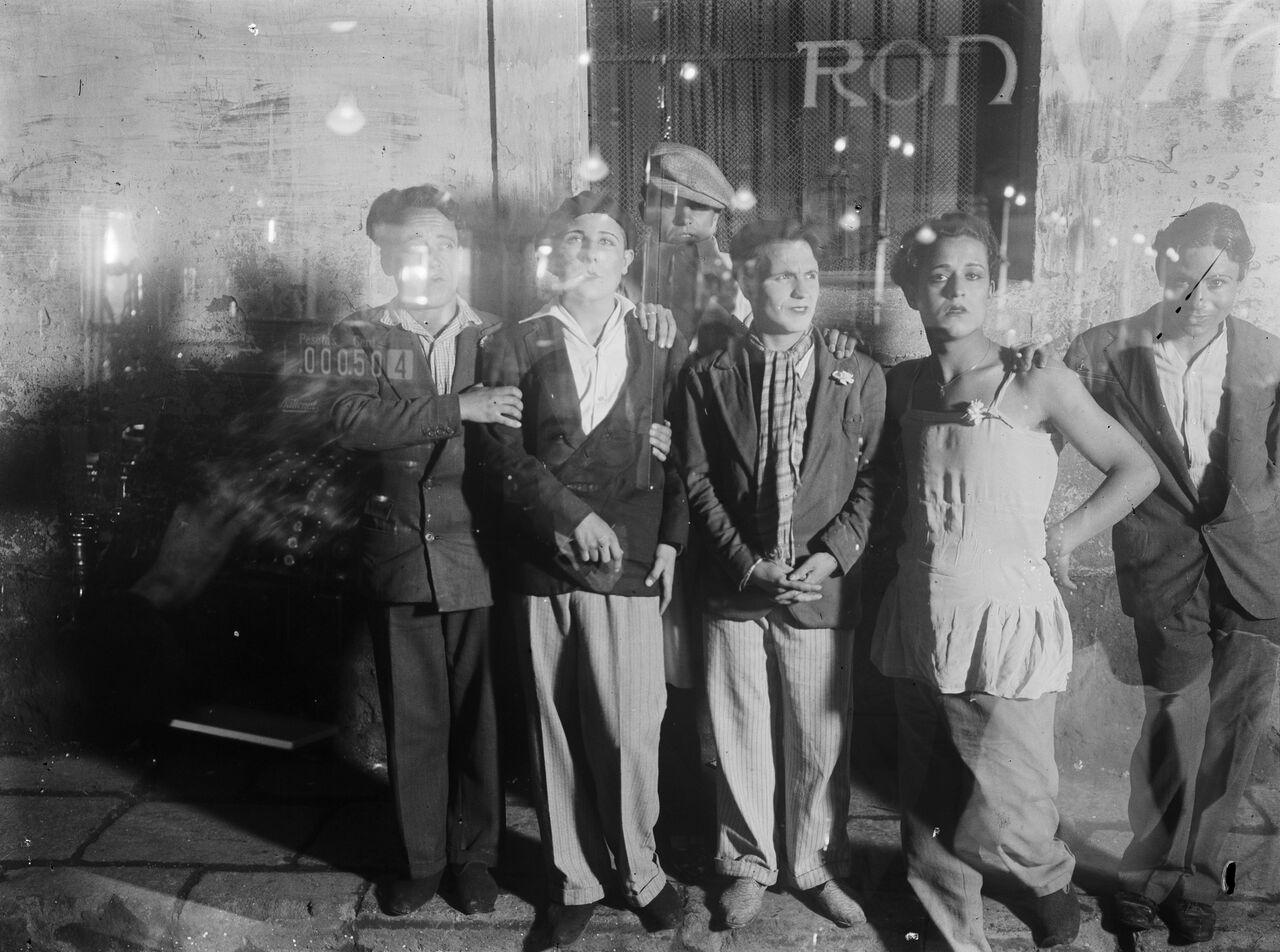 Imagen de 'Travestidos en una calle, vistos a través del vidrio de un bar, en el distrito 5, conocido popularmente como el barrio Chino, en Barcelona', de Gabriel Casas. Fotografía cortesía de Núria Casas i Formiguera y Archivo Nacional de Cataluña.